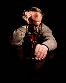 Drinking and smoking. Depressed man in a sombre mood smokes a cigarette and drinks a glass of alcohol. Both alcohol and tobacco are addictive substanc...