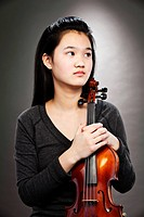 Portrait of young Asian teenage girl holding violin