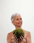 Senior woman holding plant, studio shot