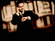Mobile telephone. Businessman looking at his wrist watch while speaking on a cellular or mobile telephone outdoors. These telephones use low_power rad...