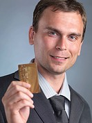 Smiling businessman holding a gold credit card in his hand, portrait