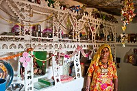 Indian woman wearing a traditional sari standing in her kitchen next to an ornate shelf containing household appliances, Thar Desert, Rajasthan, India...