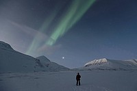 Person carrying a rifle is admiring the Northern lights and the starry sky, Spitsbergen, Svalbard, Norway, Europe