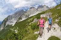Hikers walking on the hiking path connecting Gruttenhuette mountain lodge and Ellmauer Halt, Wilder Kaiser mountain, Tyrol, Austria, Europe