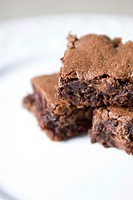 A stack of three gooey, freshly-baked chocolate brownies