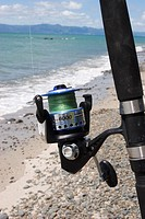 A fishing reel with a beach in the background