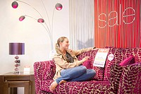 Woman sitting on couch in store