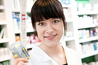This picture shows a young caucasian woman with brown hair pharmacist holding a belgian Social Security Card called Carte SIS / SIS_kaart in her hand