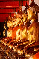 Row of sitting Buddha statues in Buddhist temple Wat Pho