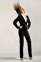 Fashionable woman is wearing a classic black pantsuit and flipping her long blond hair