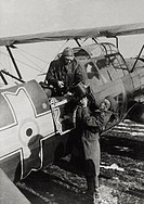 Airman giving a movie camera to a pilot of a Romanian reconnaissance plane heading behind the Russian lines of Don River. May 1943