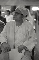 A man wearing spectacles and dressed in white linen seatedamong the public at a meeting between Pope Paul VI and thereligious non Christians of India....