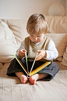 child studying childrens book sitting on couch, 1 year old boy