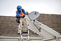 A technician installs a satellite dish on the roof of a newly purchased home in Laguna Niguel, CA. A satellite dish is a dish_shaped type of parabolic...