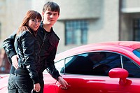 Happy young couple with a sports car