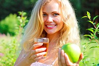 Beautiful girl is holding an apple and juice