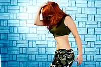 Hip hop girl dancing in modern style over urban blue brick wall