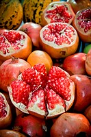 Pomegranates which some of them are sliced on a counter of an open marketplace