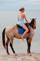 Girl rides on horse, sport and spare time on the beach