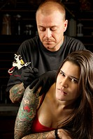 A tattoo artist applying his craft onto the back and arm of a female in her 20´s. Focus on female´s face Property release for tattoo artwork attached
