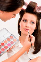 Make_up artist woman fashion model apply lipstick from color palette