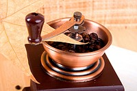 Coffee grinder and some scattered on the surface of a table of roasted coffee beans