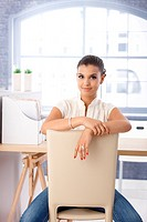 Attractive girl sitting conversely on chair on bright office.