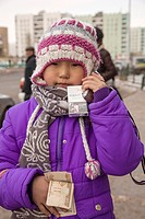 Six year old girl deals with cigarettes, cell phone and money, Erdernet, Mongolia
