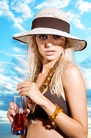 beauty portrait of graceful blond girl with summer hat and red drink