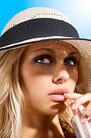 beauty portrait of graceful blond girl with summer hat drinking a fresh red