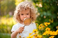 Cute child explorer flowers in garden