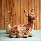 Still life of a deer statue and a vase of dried flowers