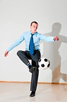 caucasian business man is playing football at office near gray wall