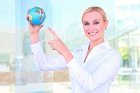 A beautiful young blonde woman holding a globe at office building