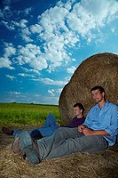 Two young men sitting on hay bales