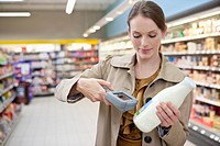 Woman checking price of milk in supermarket