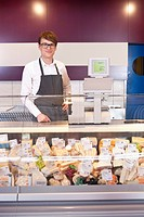 Salesman standing at counter in cheese shop