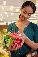 Woman choosing radish in supermarket