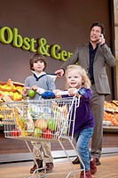 Father with two children 4_5, 6_7 doing shopping