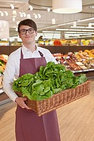 Portrait of salesman in supermarket carrying basket with lettuce