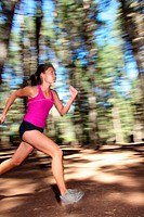 Runner, Female running fast in forest. Motíon blurred image of beautiful Asian / Caucasian woman athlete sprinting outdoors in tank top _ copy space.