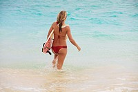teenage girl in the ocean with her surfboard at kailua beach