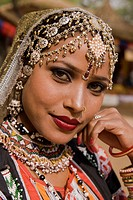 Portrait of a beautiful Indian Kalbelia dancer in ornate headdress and traditional jewelery at the Sarujkund Craft Fair in Haryana near Delhi, India.