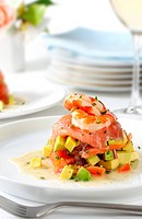 Smoked salmon with avocado salsa, topped with king prawns,