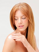 closeup portrait woman applying cream on shoulder