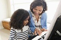 Mom instructing daughter on piano playing