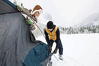 Setting up tent in the snowy countryside (thumbnail)