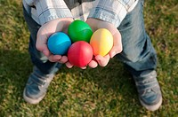 child holding four colored Easter eggs