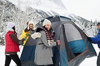Young adults setting up tent in winter.