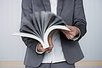 Close up of businessman's hands browsing book